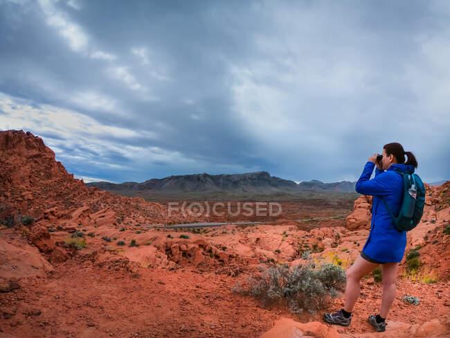 Senderista mirando a través de prismáticos, Utah, Estados Unidos - foto de stock