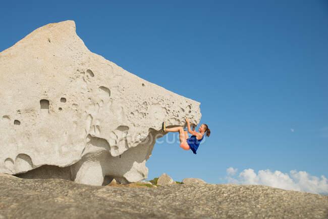 Mulher escalada em rocha pedregulho natural na praia, Córsega, França — Fotografia de Stock