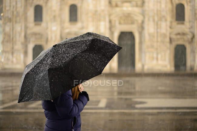 Vista lateral de uma mulher com um guarda-chuva na chuva, Itália — Fotografia de Stock