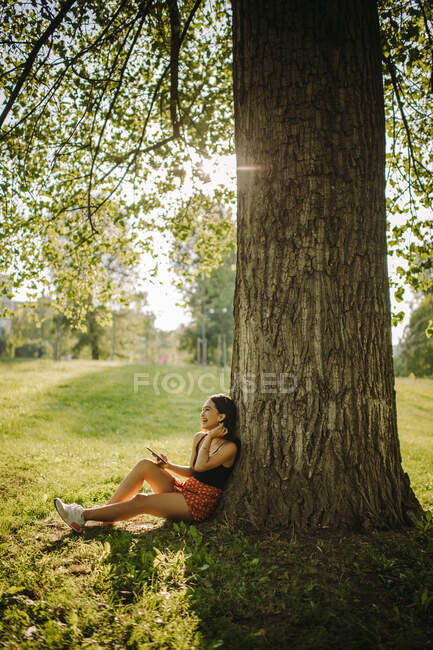 Mujer sentada bajo un árbol mirando su teléfono móvil, Serbia - foto de stock