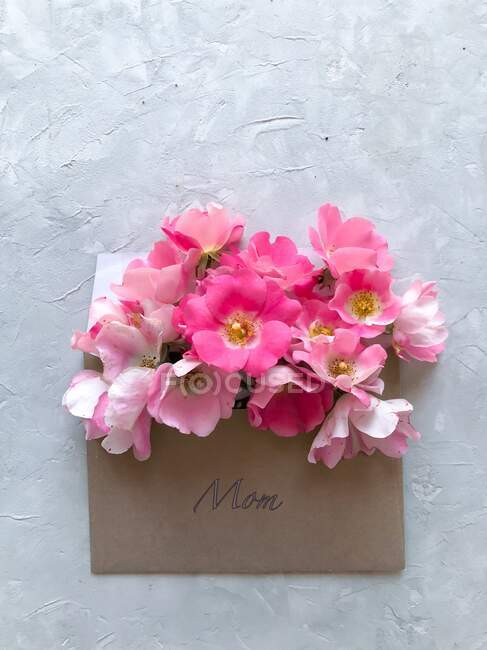 Pink flowers in an envelope marked mom for mother's day — Stock Photo