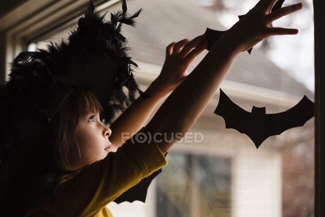 Девушка в шапке ведьмы расклеивает украшения на Хэллоуин — стоковое фото