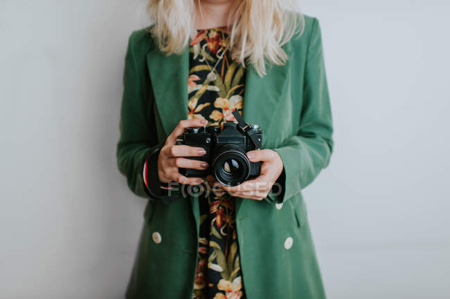 Woman in green jacket holding vintage camera — Stock Photo