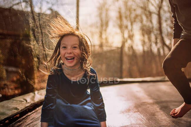 Sorrindo menina em um trampolim com seu irmão, EUA — Fotografia de Stock