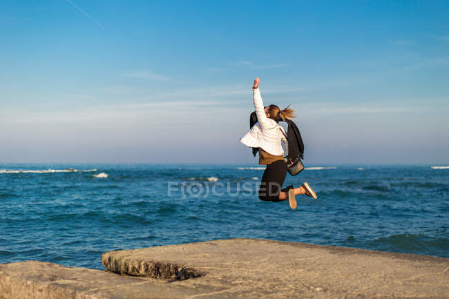 Woman jumping in the air on the beach, Italy — Foto stock