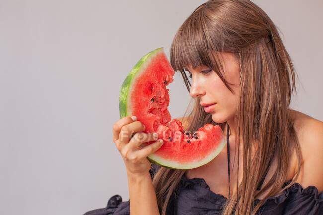 Woman looking at a slice of watermelon — Stock Photo