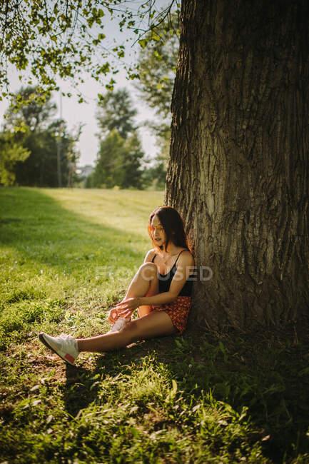 Женщина сидит под деревом в парке, Сербия — стоковое фото