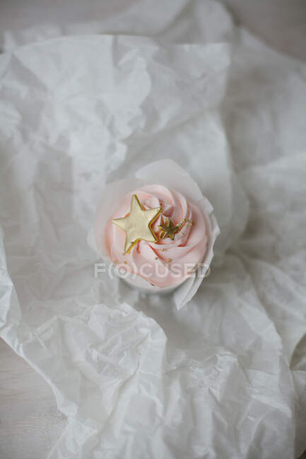 Cupcake with gold colored decorations on parchment — Stock Photo