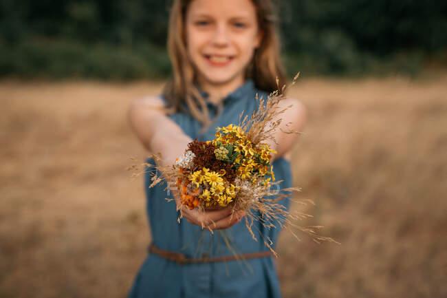 Ragazza sorridente in piedi in un campo che tiene un mazzo di fiori selvatici, Paesi Bassi — Foto stock