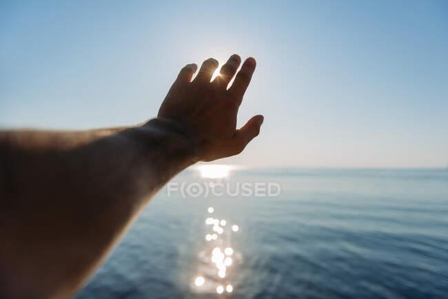 Рука людини тягнеться до сонця. — стокове фото
