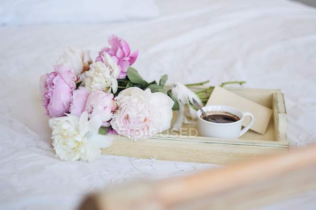 Bouquet of peonies and a cup of coffee with an envelope on a tray on a bed — Stock Photo