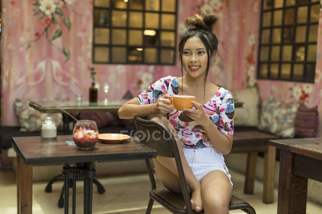 A young asian woman is enjoying a colorful dessert bowl. — Stock Photo