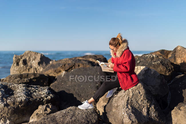 Woman sitting on rocks by the sea reading a book, Emilia Romagna, Italy — Foto stock