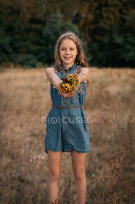 Смолящая девочка, стоящая в поле с букетом полевых цветов, Нидерланды — стоковое фото