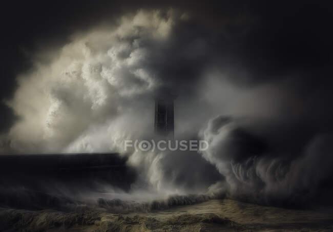 Olas estrellándose contra un faro y un muro de mar, italia - foto de stock