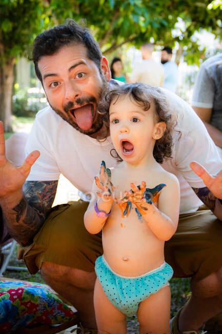 Батько і дочка малюють і висміюють обличчя. — стокове фото