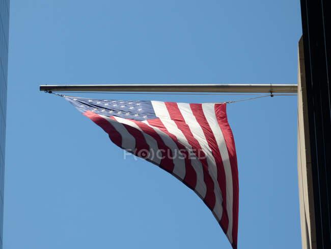 Американский флаг против голубого неба, Манхэттен, Нью-Йорк, США — стоковое фото