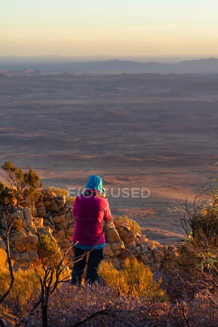 Mulher de pé no Monte Sonder tirar uma foto ao nascer do sol, West MacDonnell National Park, Território do Norte, Austrália — Fotografia de Stock