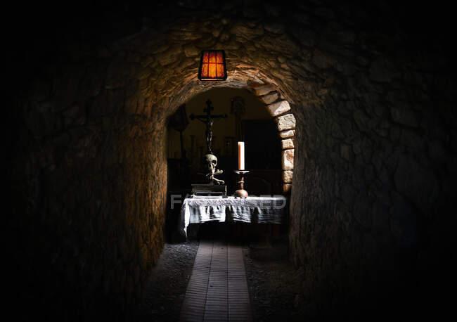 Una mesa con una vela y un cráneo en un sótano - foto de stock