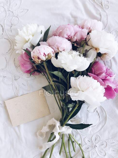 Bouquet of peonies with a blank envelope — Stock Photo
