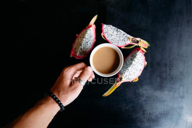 Рука людини, що тримає чашку чаю і клин дракона. — стокове фото