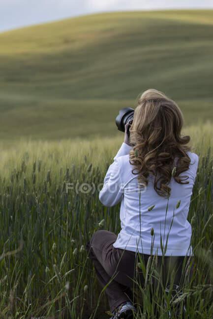 Mujer agachada en un prado tomando una foto, San Quirico d 'Orcia, Siena, Toscana, Italia - foto de stock