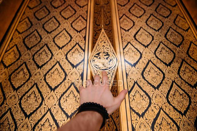 Мужская рука касается украшенной стены в храме, Бангкок, Таиланд — стоковое фото