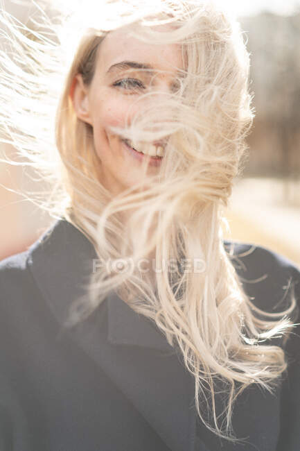 Portrait of a smiling woman with windswept hair — Stock Photo