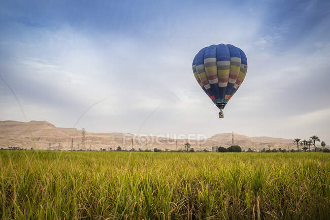 Hot air balloon flying over Valley of the Kings, Luxor, Egypt — Stock Photo