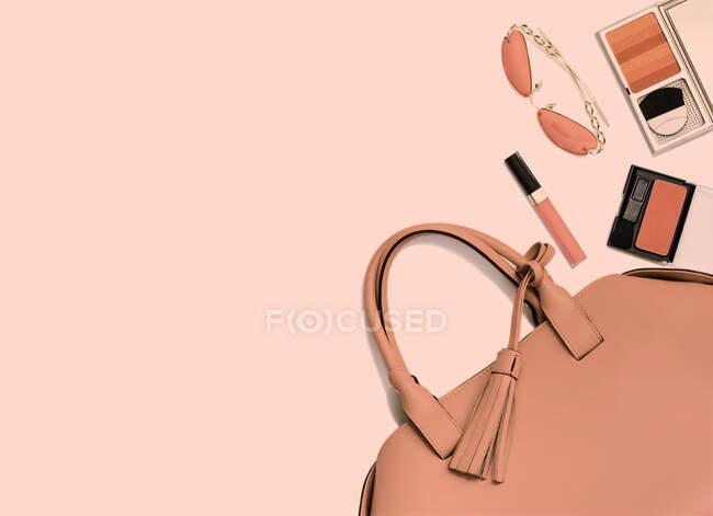 Bolso de mujer, maquillaje y gafas de sol en color coral tendencia de 2019 - foto de stock