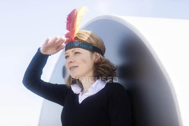 Женщина, одетая в североамериканский племенной костюм, прикрывая глаза, Германия — стоковое фото