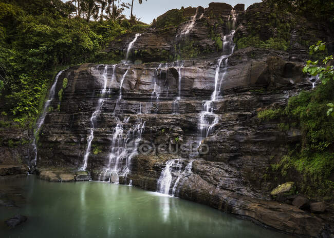 Rocks with flowing waterfalls in green lake water — Stock Photo