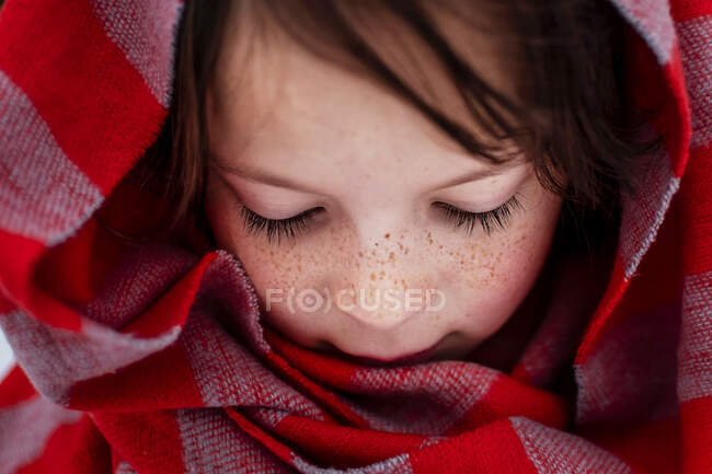 Portrait of a girl standing in snow wearing a scarf around her head, United States — Stock Photo