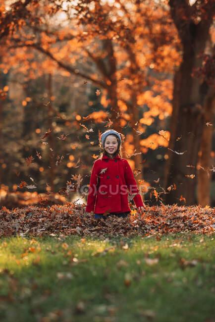 Ragazza che lancia foglie autunnali in aria, Stati Uniti — Foto stock