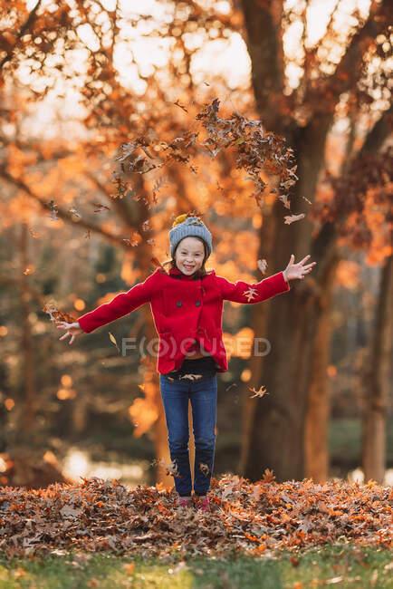 Chica lanzando hojas de otoño en el aire, Estados Unidos - foto de stock