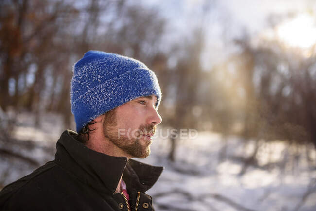 Portrait of man with snow on hat in winter outdoor scene — Stock Photo