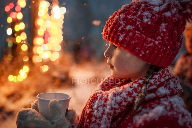 Girl standing outdoors holding a hot chocolate drink, United States — Stock Photo