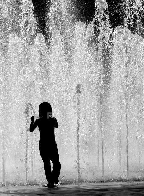 Ragazzo saltando in acqua con spruzzi — Foto stock