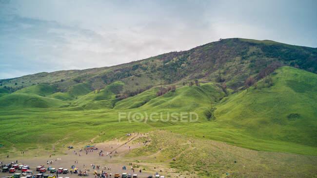 Картинный вид на парковку с машинами на зеленом фоне гор — стоковое фото