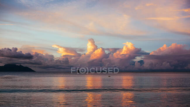 Beautiful sunset sky reflecting in sea water with distant rocks — Stock Photo