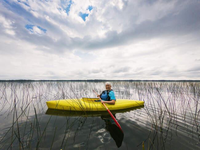 Femme âgée souriante kayak sur un lac, États-Unis — Photo de stock
