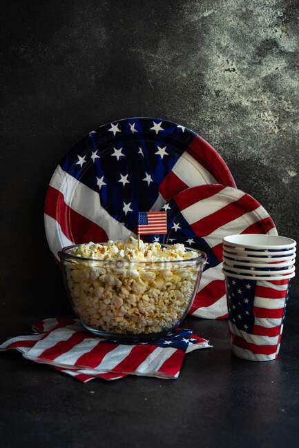 Чаша попкорна и одноразовые тарелки, чашки и салфетки ко Дню Независимости — стоковое фото