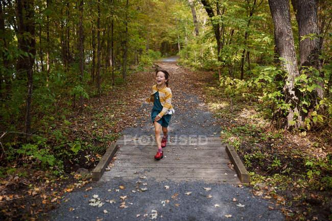 Дівчинка перебігає невеликий пішохідний міст (США). — стокове фото