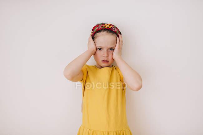 Retrato de una chica cansada frotándose la cara sobre fondo blanco - foto de stock