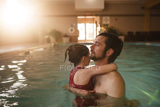 Padre sosteniendo a su hija en una piscina - foto de stock