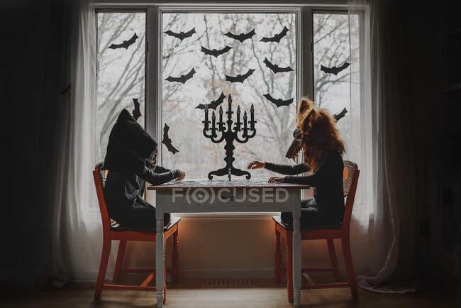 Duas crianças em trajes de Halloween sentadas perto de uma janela fazendo um quebra-cabeça, Estados Unidos — Fotografia de Stock