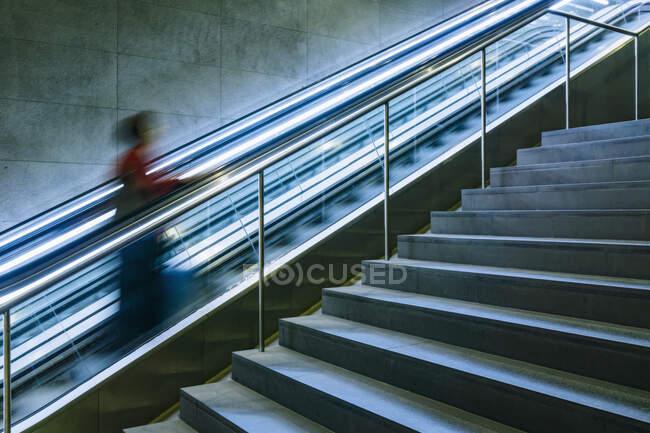 Frau steigt Rolltreppe hinauf — Stockfoto