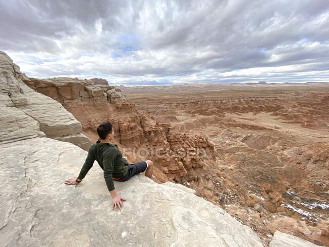 Uomo seduto sulla scogliera, Goblin Valley State Park, Utah, USA — Foto stock