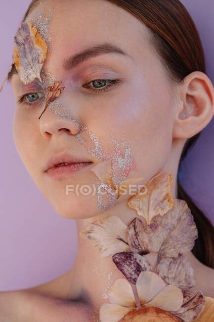 Conceptual beauty portrait of a woman with dried flowers on her face — Stock Photo