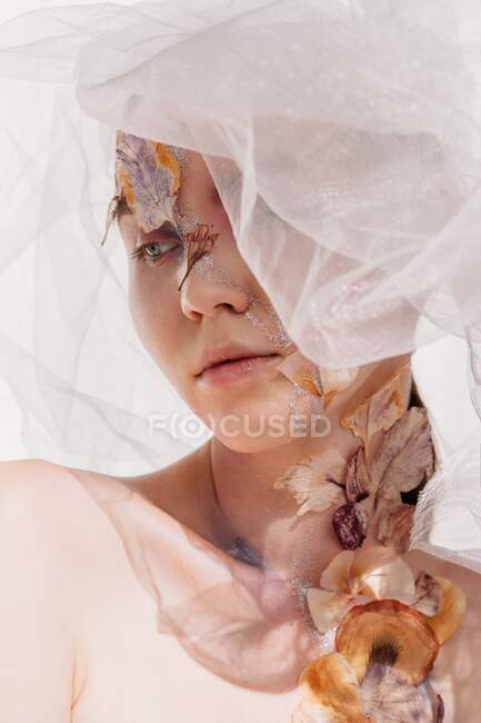 Conceptual beauty portrait of a woman wearing a veil with dried flowers on her face and neck — Stock Photo